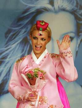 "U.S. pop singer Britney Spears waves to photographers,  wearing South Korea's traditional costume 'Hanbok' during a photo session in Seoul, Monday, Dec. 8, 2003. Spears arrived in South Korea Sunday for her Asia tour to promote her new album, ""In the Zone."" Photo: LEE JIN-MAN, AP / AP"