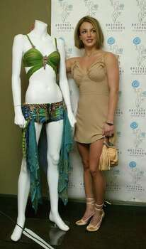 Pop singer Britney Spears poses for photographers beside an auction piece at a press conference Thursday, May 22, 2003, in New York. Spears announced the kickoff of her first online charity auction of memorabilia that includes her costumes, childhood items, and signed photographs and posters. Photo: ROBERT SPENCER, AP / AP