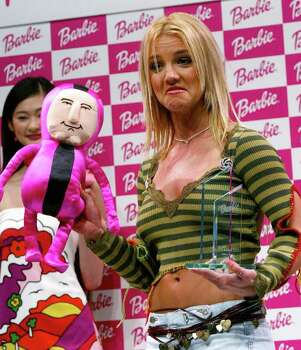 "** RETRANSMISSION TO CLARIFY THAT AWARD IS FOR WOMAN ADMIRED, NOT LONGED FOR ** Pop star Britney Spears makes face as she mimics a Shigeshige Shigeo, a character doll of Japanese toy maker Bandai Co., during an award ceremony in Tokyo on Sunday, April 21, 2002. The American singer, in town for a Japan premiere of her film ""Not a Girl"" and a concert, was given the Barbie Award 2002 for the woman most admired by Japanese women. Photo: SHIZUO KAMBAYASHI, AP / AP"
