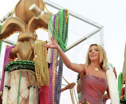 Pop singer Britney Spears tosses a cup to the crowd as she rides  on a float down Orleans Avenue Saturday, March 4, 2000, in New Orleans, during the Endymion parade. Photo: ALEX BRANDON, AP / THE TIMES-PICAYUNE