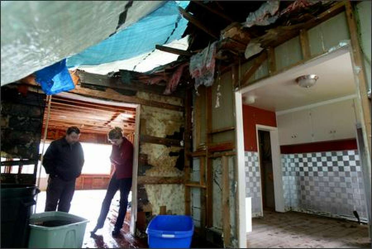 Gerard Denommee and Kathi Cronin's home remains shrouded in tarps after it was damaged by a falling poplar tree in last year's Hanukkah Eve windstorm.