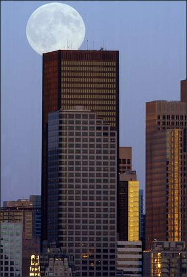 A hunter's moon comes up Thursday in downtown as sunset highlights buildings in the foreground. Photo: GRANT M. HALLER/P-I