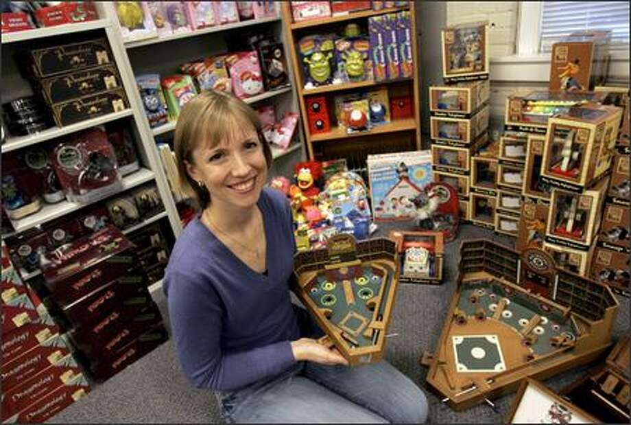 Erika Cottrell, president of Seattle-based Front Porch Classics, shows off toys and games produced by Front Porch and Sababa Toys, which recently merged. Photo: Mike Kane/P-I