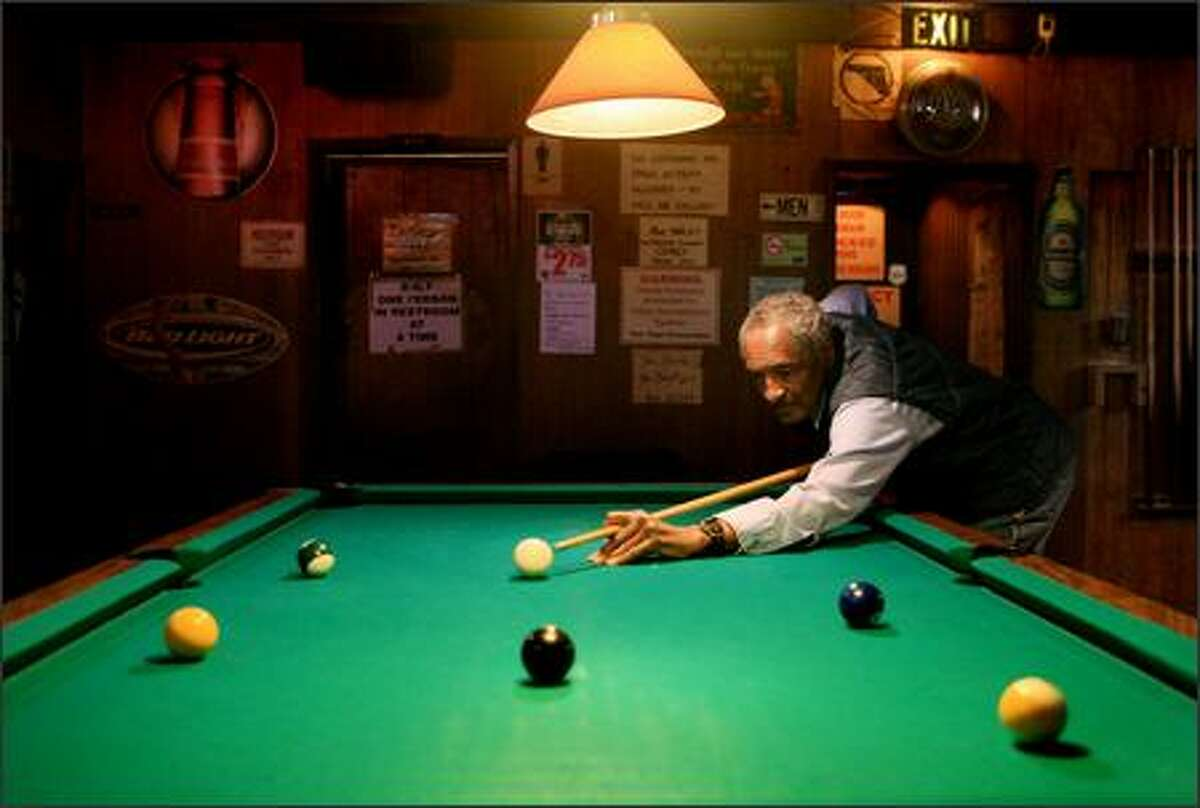 Ted Cook shoots pool Friday at Angie's Tavern. Cook says the newly upscale Columbia City seems a bit safer, but the influx of money has made it difficult for residents on a fixed income.