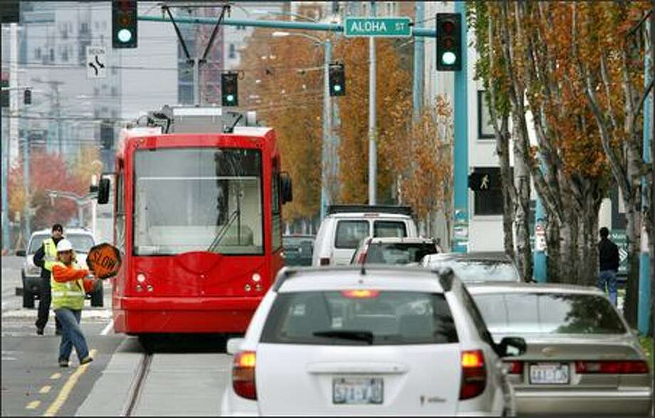 Sandy Hyde directs traffic on Fairview Avenue North around a stopped South Lake Union streetcar Monday during testing, which will last a week. Photo: Andy Rogers/Seattle Post-Intelligencer