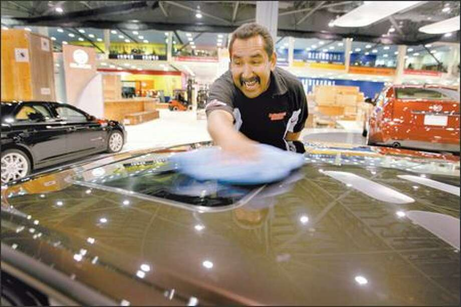 Smiley Castaneda, of Professional Detailers from Orange County, Calif., polishes a 2008 Cadillac CTS4 during setup for the Seattle International Auto Show. Photo: Scott Eklund/Seattle Post-Intelligencer