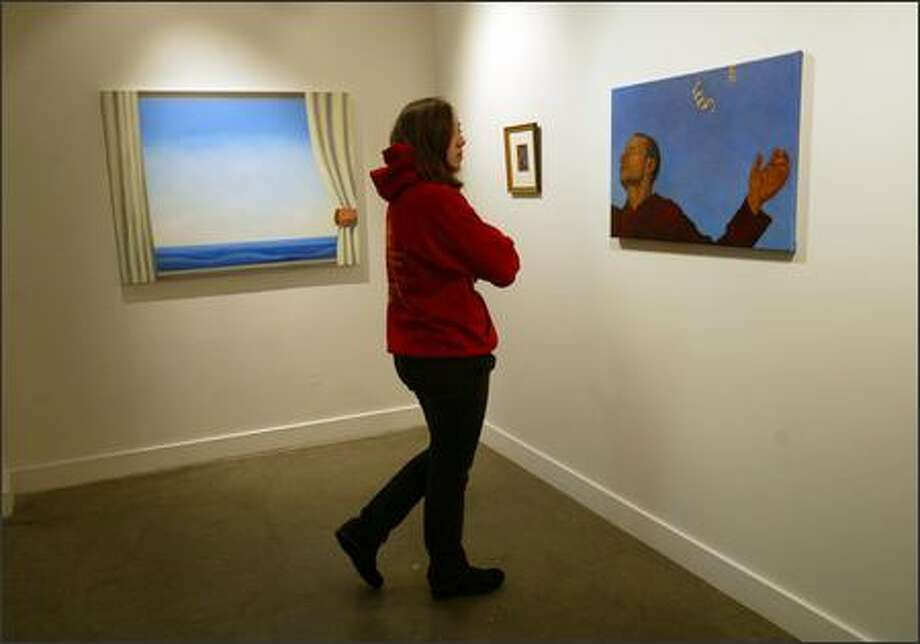 "Seattle Pacific University student Beth Burdick looks at the faculty exhibit ""Hope: Open/Closed"" at the SPU Art Center Gallery, which is open to the public through Friday. The exhibit follows the theme of the university's ""Day of Common Learning."" Photo: Karen Ducey/Seattle Post-Intelligencer"