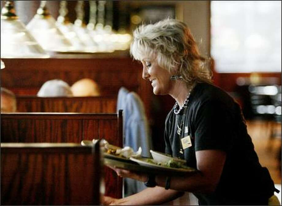 "The delightful DeDe Schumaier, a server at Sizzler in Tukwila for 23 years, is better-known as ""Mrs. Seahawk,"" and has even been inducted into the Pro Football Hall of Fame. Photo: Dan DeLong/Seattle Post-Intelligencer"