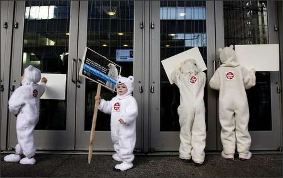 Dressed as polar bears, left to right, Finnean Broadhead, 5, Deaglan Broadhead, 3, Cian McGinn, 8, and Miyo McGinn, 10, display posters to those gathered inside Benaroya Hall for the U.S. Conference of Mayors climate change summit during a demonstration Thursday in Seattle. The children's parents are members of Citizens against RTID (Regional Transportation Investment District), an activist group that opposes the passage of Proposition 1 in Tuesday's election. Photo: Andy Rogers/Seattle Post-Intelligencer