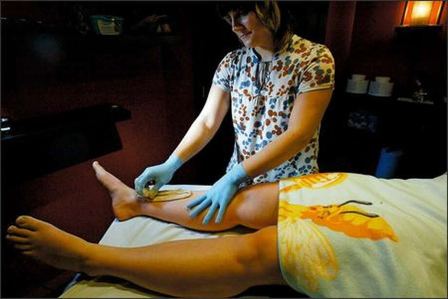 Sugarist De Ane Price removes hair from a client's legs using a sugar paste at The Sweet Spot in Fremont. Photo: Karen Ducey/Seattle Post-Intelligencer