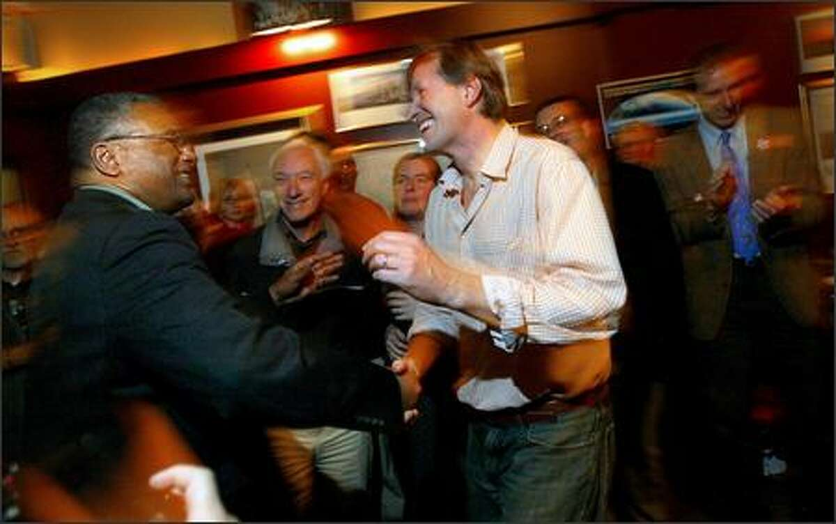 King County Executive Ron Sims, left, congratulates Mike O'Brien, president of the Northwest Chapter of the Sierra Club, at a gathering Tuesday night of opponents at Piecora's Pizza and Pasta in Seattle.
