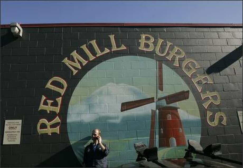 "Greg Odle, a BMW mechanic who works in Seattle and lives in Tukwila, talks on the phone Thursday outside of Red Mill Burgers in Magnolia, which bans cell phones inside. ""If they don't want cell phone use, I respect that,"" Odle said. Red Mill has banned cell phones since 1995. Photo: Mike Kane/P-I"