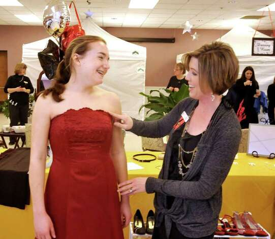 Kristen Mueller, 18, tries on a prom dress with help from Heidi Finlay, who organized the Pretty for Prom sale at the New Fairfield firehouse, Saturday, March 12, 2011. Photo: Michael Duffy / The News-Times