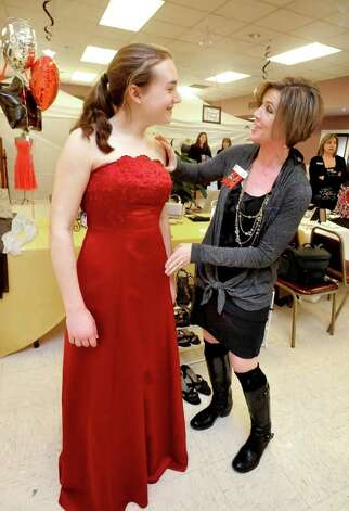 Kristen Mueller, 18, tries on a prom dress, with help from Heidi Finlay, who organized the Pretty for Prom sale at the New Fairfield firehouse, Saturday, March 12, 2011. Photo: Michael Duffy / The News-Times