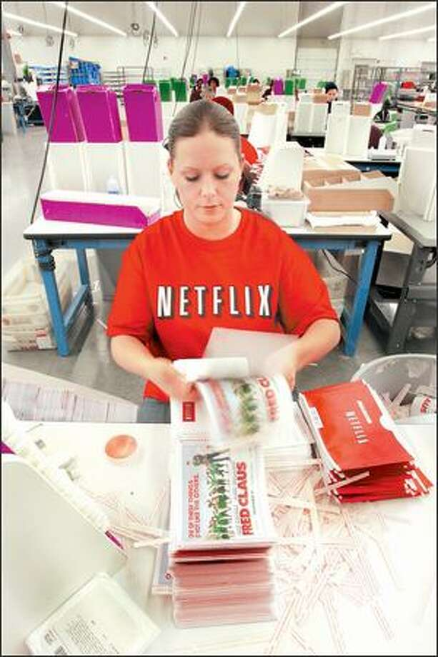 "Diana Carlson stuffs mailers with DVDs at the Netflix warehouse near Tacoma on Monday. Carlson is one of the fastest stuffers, with a record of 900-plus DVDs an hour. The average is about 650 DVDs per hour. ""The Tacoma site is the best,"" supervisor Christi Lewis said. ""We're a very tightly bonded crew."" Photo: Gilbert W. Arias/Seattle Post-Intelligencer"