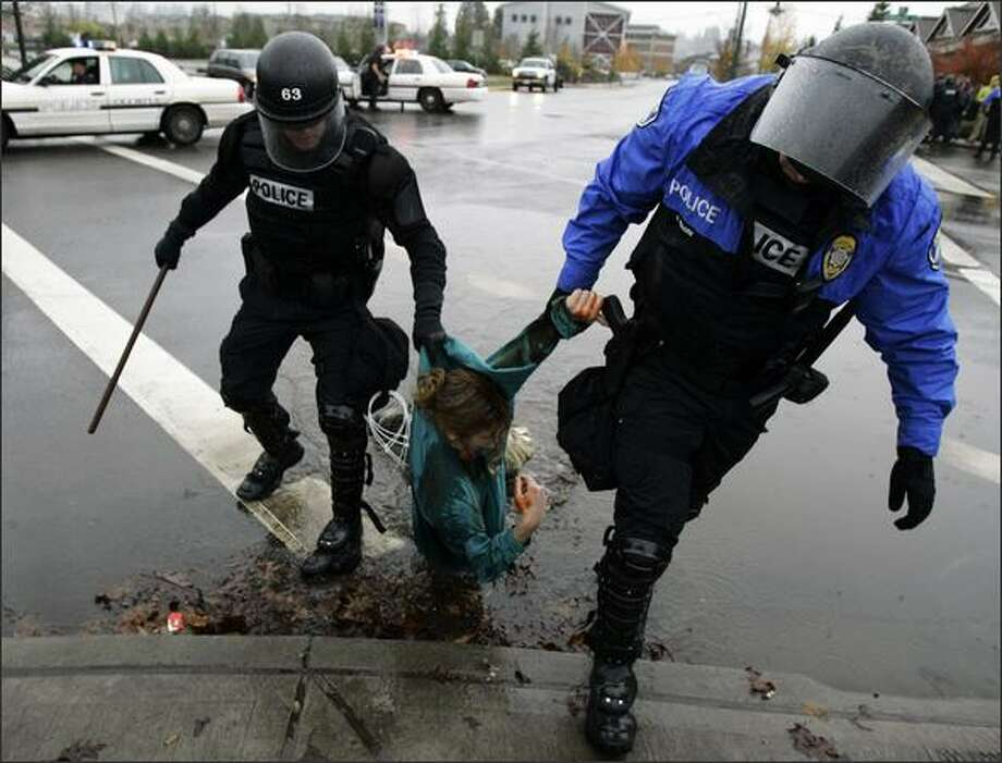 Olympia police officers drag to the sidewalk Thursday a protester who had tried to block the entrance to the Port of Olympia. Five people, but not the woman pictured, were arrested in the anti-war demonstration. Photo: / Associated Press