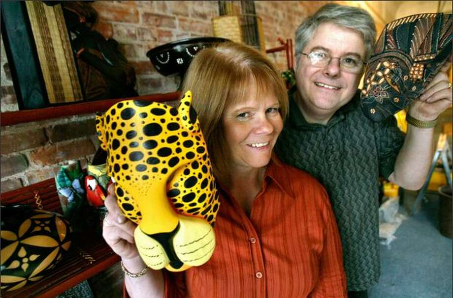 Tammy and Andy James show off decorative masks and other goods they will sell at their new Ballard store, Market Street Traders. Photo: Andy Rogers/Seattle Post-Intelligencer
