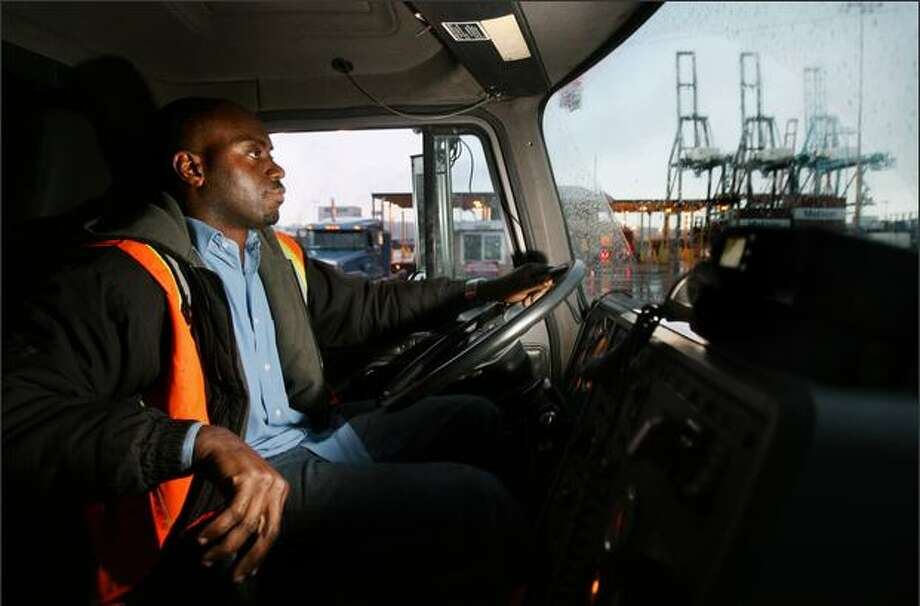 Olufemi Dosunmu, an independent trucker at the port, drives on East Marginal Way South while delivering a shipping container Thursday. Photo: Dan DeLong/Seattle Post-Intelligencer