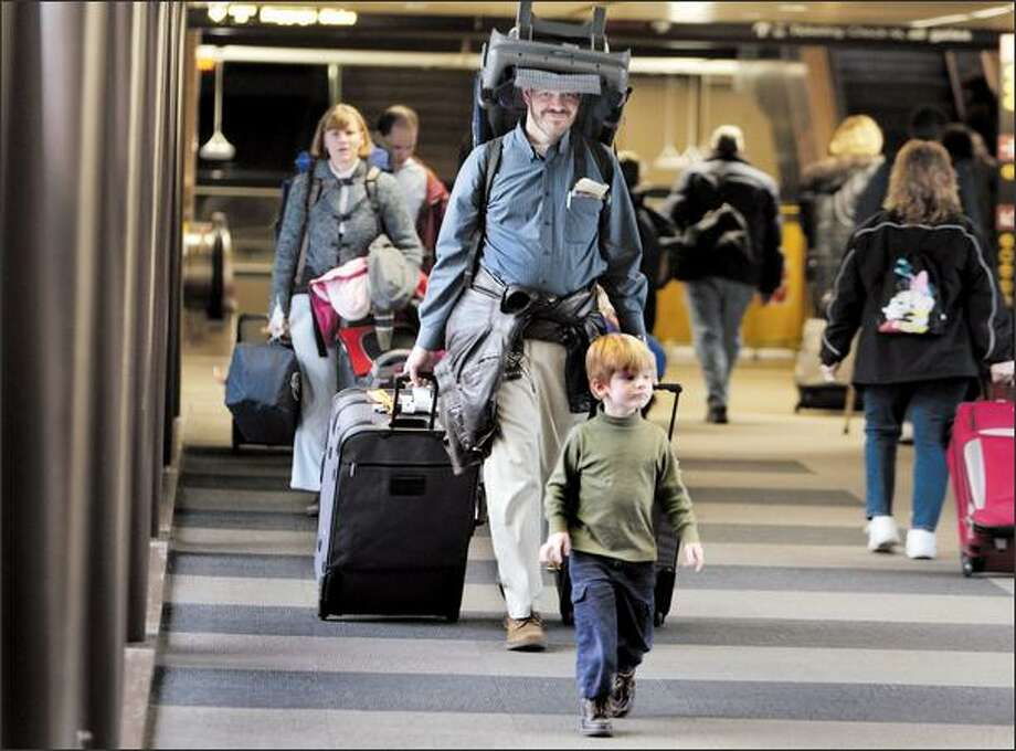 John Kempen, his son, Christopher, 3, foreground, his wife, Lori, trailing, and his daughter, Natalie, 1, leave SeaTac airport after arriving from Philadelphia on Monday. They are visiting Kempen's family in Seattle. Kempen said the flight in from Philadelphia was about half full, and that carrying the car seat on his head was comfortable. Photo: Meryl Schenker/Seattle Post-Intelligencer