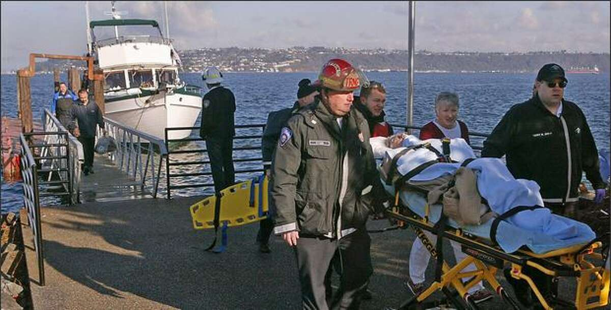The passenger from the small plane that went into Commencement Bay after a collision over Tacoma is wheeled to an ambulance Tuesday. In the background is the boat that rescued the two people aboard.