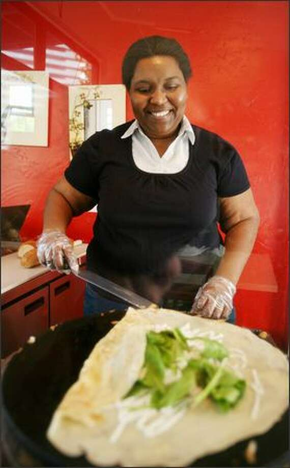 """Aissa Diouf makes La Reine, the """"Queen of Crepes,"""" with chicken, tomatoes, bacon, Swiss cheese, spinach and a special sauce. Diouf is the owner and only employee. Photo: Paul Joseph Brown/Seattle Post-Intelligencer"""