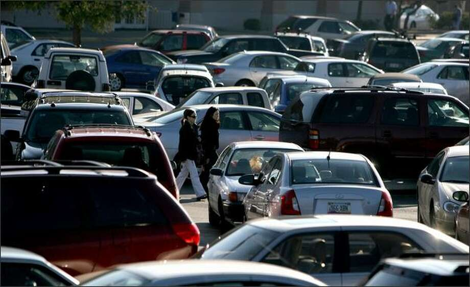 Shoppers at Westfield Southcenter Mall returns to their car Wednesday. One way to beat car prowls in parking lots is to lock valuables in the trunk -- and not go back inside the mall without moving the car. Photo: Scott Eklund/Seattle Post-Intelligencer
