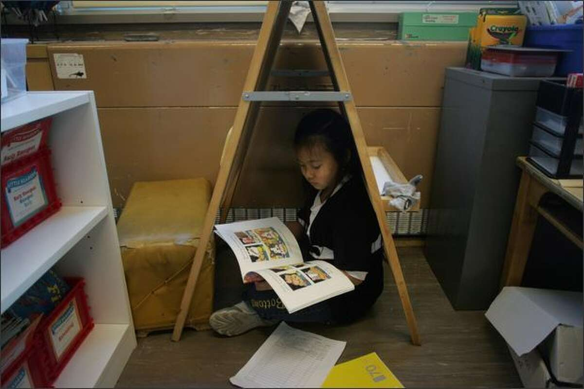 Jessie Nguyen, 7, picks a secluded spot to read Wednesday during a second-grade reading and writing class at Van Asselt Elementary in Seattle.