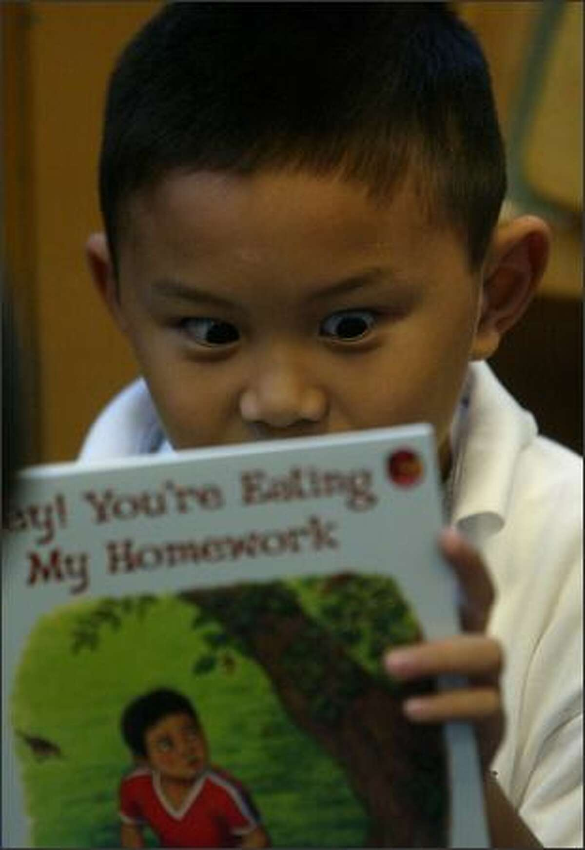 Second-grader Kevin Marin, 7, is riveted by a book. The Seattle district lets young students pick reading material at their level.