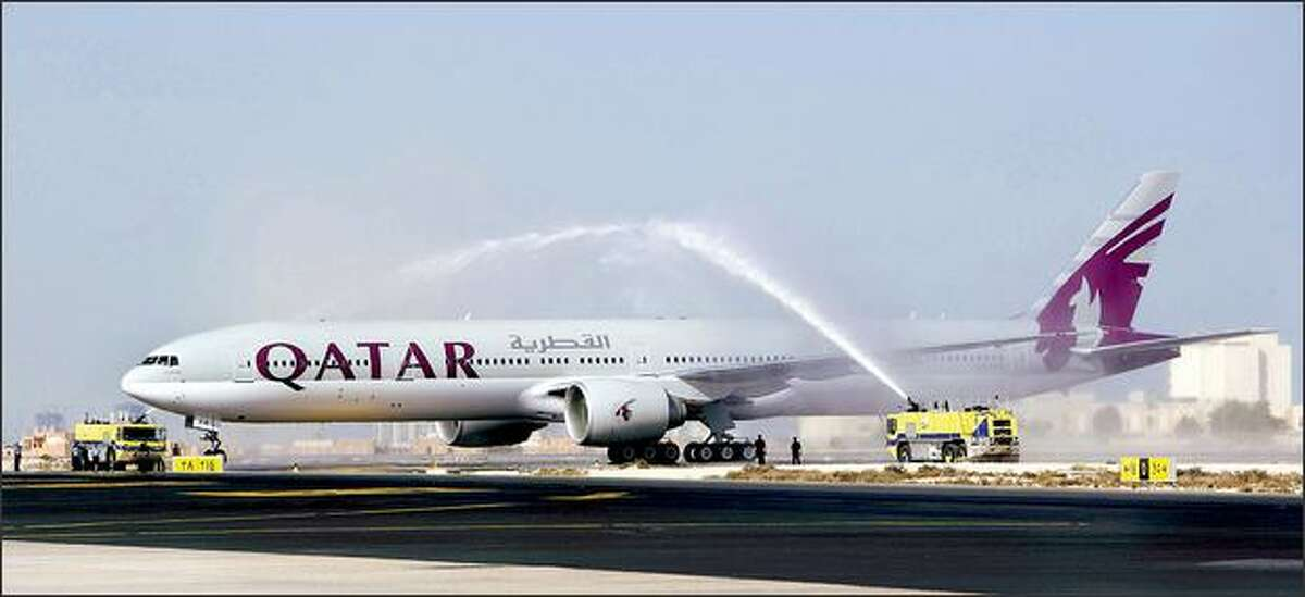 A Boeing 777-300ER gets a water-cannon salute Thursday in Doha, Qatar, after a flight from Everett. It is Qatar Airways' first Boeing jet in a fleet of Airbus planes, with 56 Boeing jets on order. (QATAR AIRLINES PHOTOS)