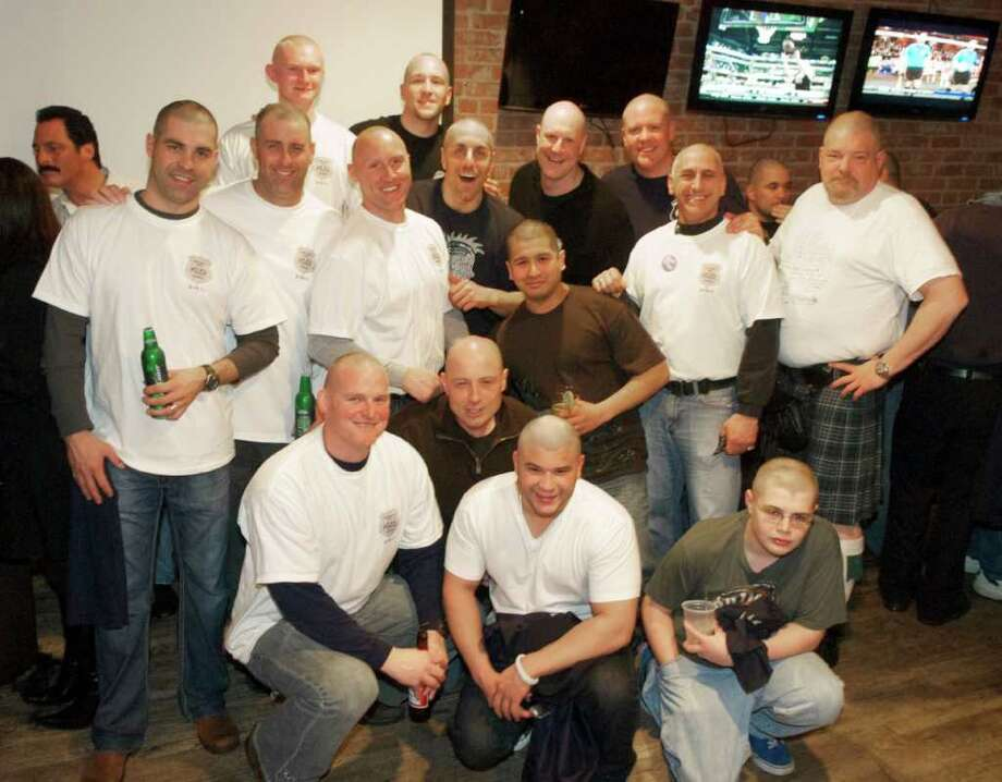 More than a dozen Greenwich police officers shaved their heads during a recent fundraising event to benefit the St. Baldrick's Foundation. The event, which was held at the Bradford's Grill and Tavern in Stamford, raised about $20,000 in total. Greenwich police raised $3,790 among the officers who participated, which included patrolman, detectives and even a police captain. Some of the officers' sons participated as well. Officer Ernest Mulhern helped organize the police department's involvement. The St. Baldrick's Foundation is a charity committed to funding research to help infants, children, teens and young adults fighting childhood cancers. Photo: Contributed Photo / Greenwich Time Contributed