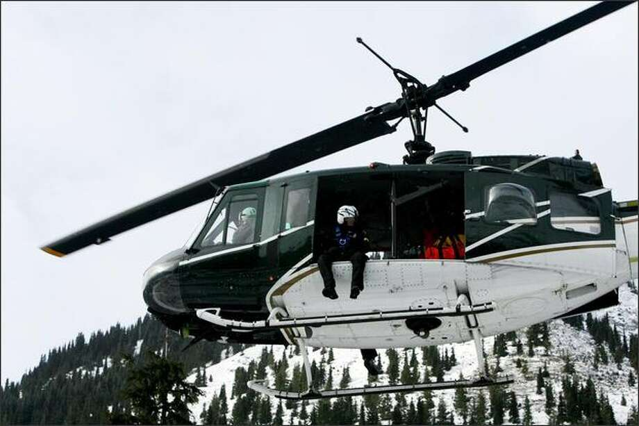 A helicopter from the King County Sheriff's Office helps in the search for three missing snowboarders Thursday on Crystal Mountain. Photo: Scott Eklund/P-I