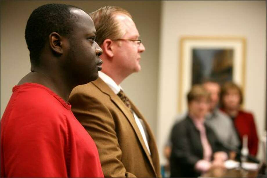 Lamin Darboe and his attorney, Gene Piculell, listen Friday in King County Superior Court to a statement from relatives of the woman Darboe was convicted of raping. Photo: Paul Joseph Brown/Seattle Post-Intelligencer