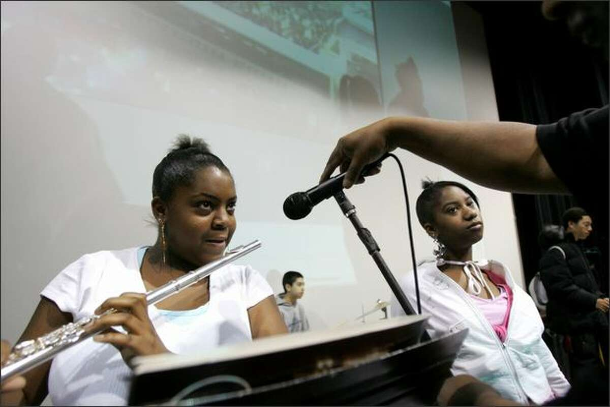 April Miller, 14, sound-checks her flute while band director Clarence Robinson adjusts her microphone before an assembly at Rainier Beach High School on Wednesday. At right is clarinet player Deshonae Williams, 14. The school is emphasizing its performing arts and academic programs.