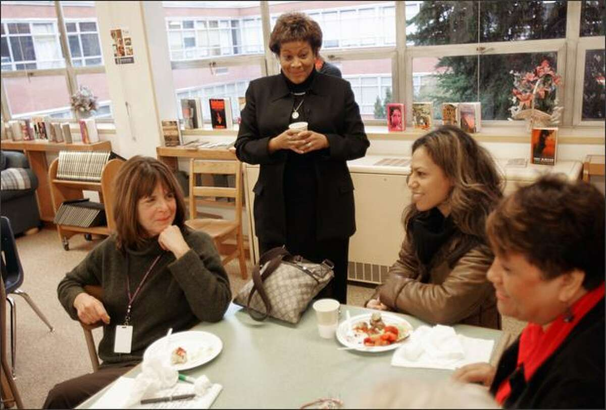 """Superintendent Maria Goodloe-Johnson, standing, meets, from left, substitute Nancy Anderson, family support worker Virginia Owens and ninth-grade intervention specialist Betty Patu during a congratulatory breakfast at Rainier Beach on Wednesday. Goodloe- Johnson said she doesn't let negative remarks about the school go unchecked. """"I ask them, 'When's the last time you went there?' """""""