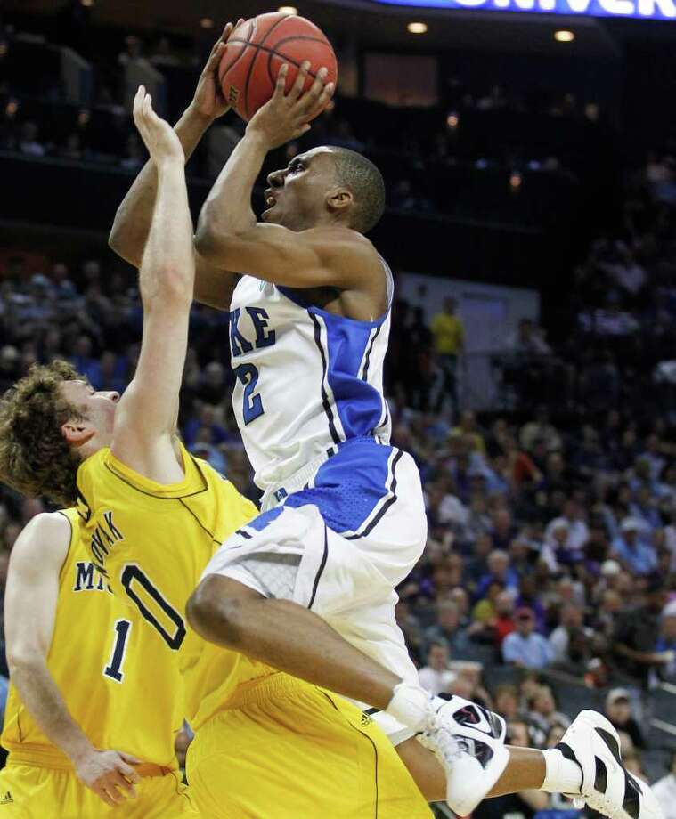 Duke guard Nolan Smith (2) shoots as Michigan's Zack Novak (0) falls back in the first half of a West Regional NCAA tournament third-round college basketball game, Sunday, March 20, 2011, in Charlotte, N.C. (AP Photo/Bob Leverone) Photo: AP