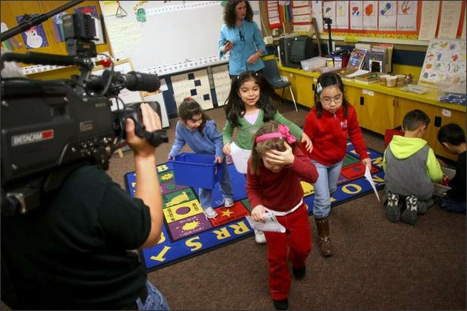 Maple Elementary kindergarten students, from left, Elizabeth Chavez-Mendoza, Andrea Rodas Garcia, Valeria Grasso and Vivian Vo walk past the camera Tuesday. Photo: Mike Kane/P-I