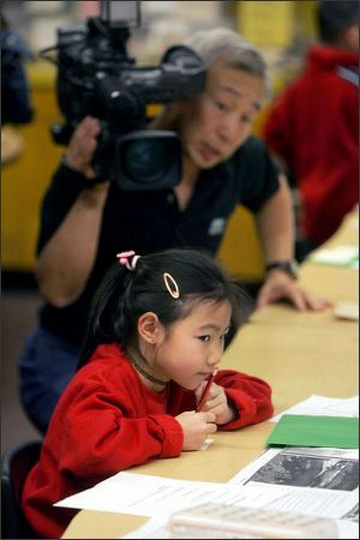 Maple Elementary first-grader Lorena Ng looks up as freelance cameraman Danny Chen works on an Education Department film.