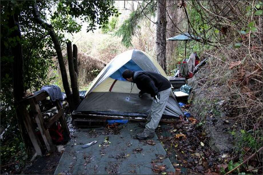 Ameen Salh, grounds maintenance worker with Seattle Parks and Recreation, announces his presence at a homeless encampment on the slopes just north of Elliott Avenue on Wednesday. Photo: Gilbert W. Arias/Seattle Post-Intelligencer
