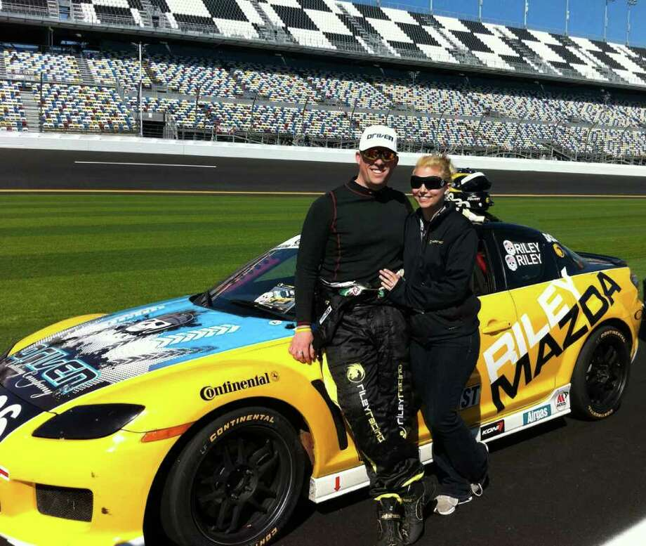 Jameson Riley, 25, and Jessica Lombardi, 26, standing in front of the Riley Racing Mazda RX-8 at Daytona International Speedway in late January 2011, competing in the NASCAR owned Grand-Am Continental Tire Sports Car Challenge endurance series. Photo: Contributed Photo / Stamford Advocate Contributed