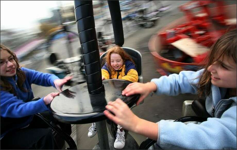 Alexandra Smerekanych, 11, left; Eva Smerekanych, 7; and Alysse Merila, 10, take a spin on the Tornado ride this month in the Fun Forest at Seattle Center. Photo: Paul Joseph Brown/Seattle Post-Intelligencer
