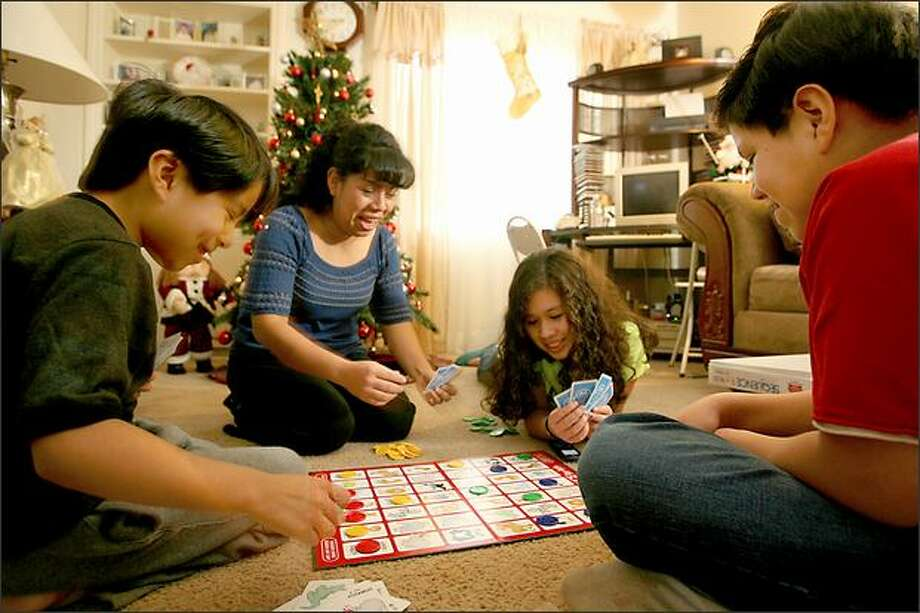 Norma Ortiz, second from left, plays at home with her children. Ortiz, an immigrant from Mexico, used New Futures to learn English after she arrived in this country four years ago. Now she works for the organization as a community developer, helping other families. Photo: Scott Eklund/Seattle Post-Intelligencer