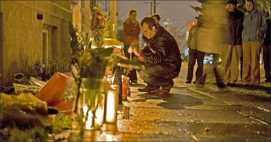 A mourner lights a candle before placing it with about sixty other candles Wednesday at the spot at 15th Ave. and E. Howell Streets where Shannon Harps was killed. Photo: Grant M. Haller/Seattle Post-Intelligencer
