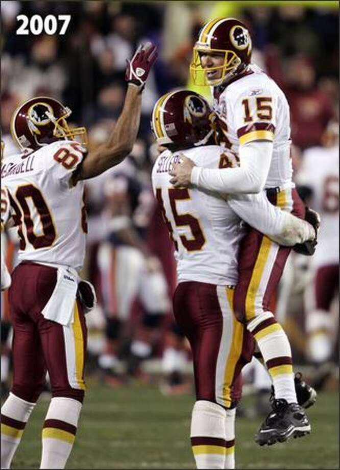Washington's Keenan McCardell gives Todd Collins a lift after Collins connected for his second touchdown pass of the day against the Chicago Bears on Dec. 6, when he subbed for an injured Jason Campbell. Photo: / Associated Press