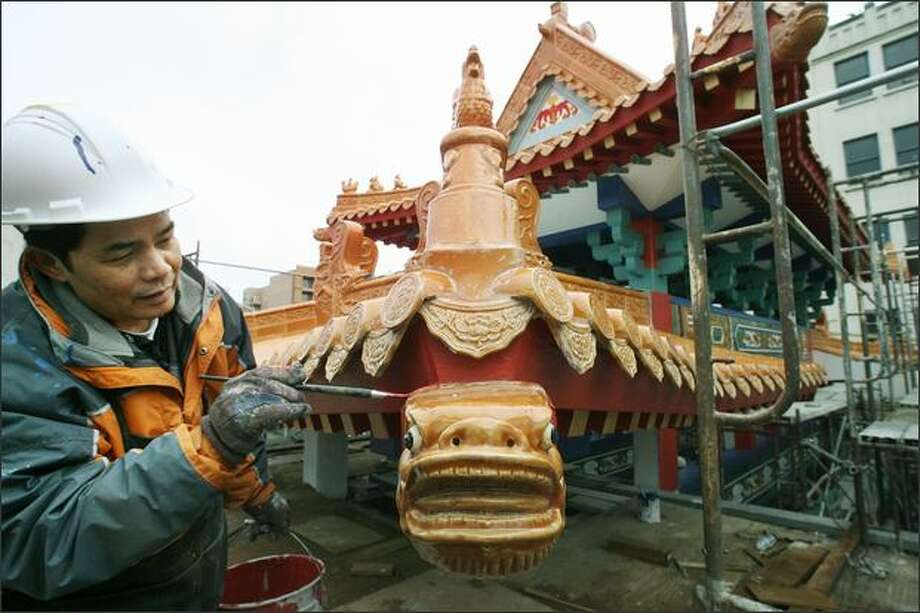 Wei Fang touches up the paint atop the new archway into old Chinatown. Photo: Dan DeLong/Seattle Post-Intelligencer