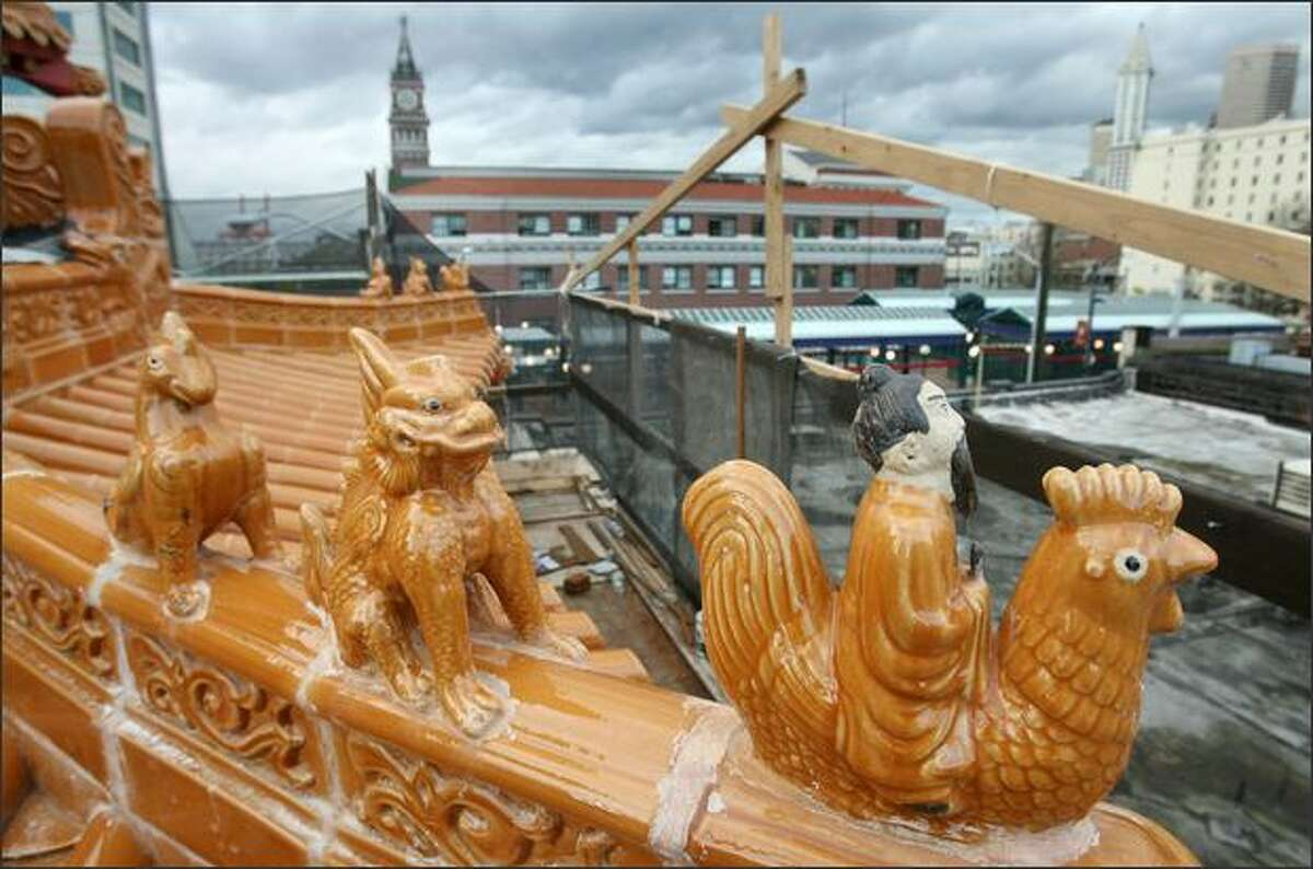 Animals such as a dragon and a phoenix atop a new gate under construction in Chinatown are said to keep away bad luck and welcome a flow of good air.