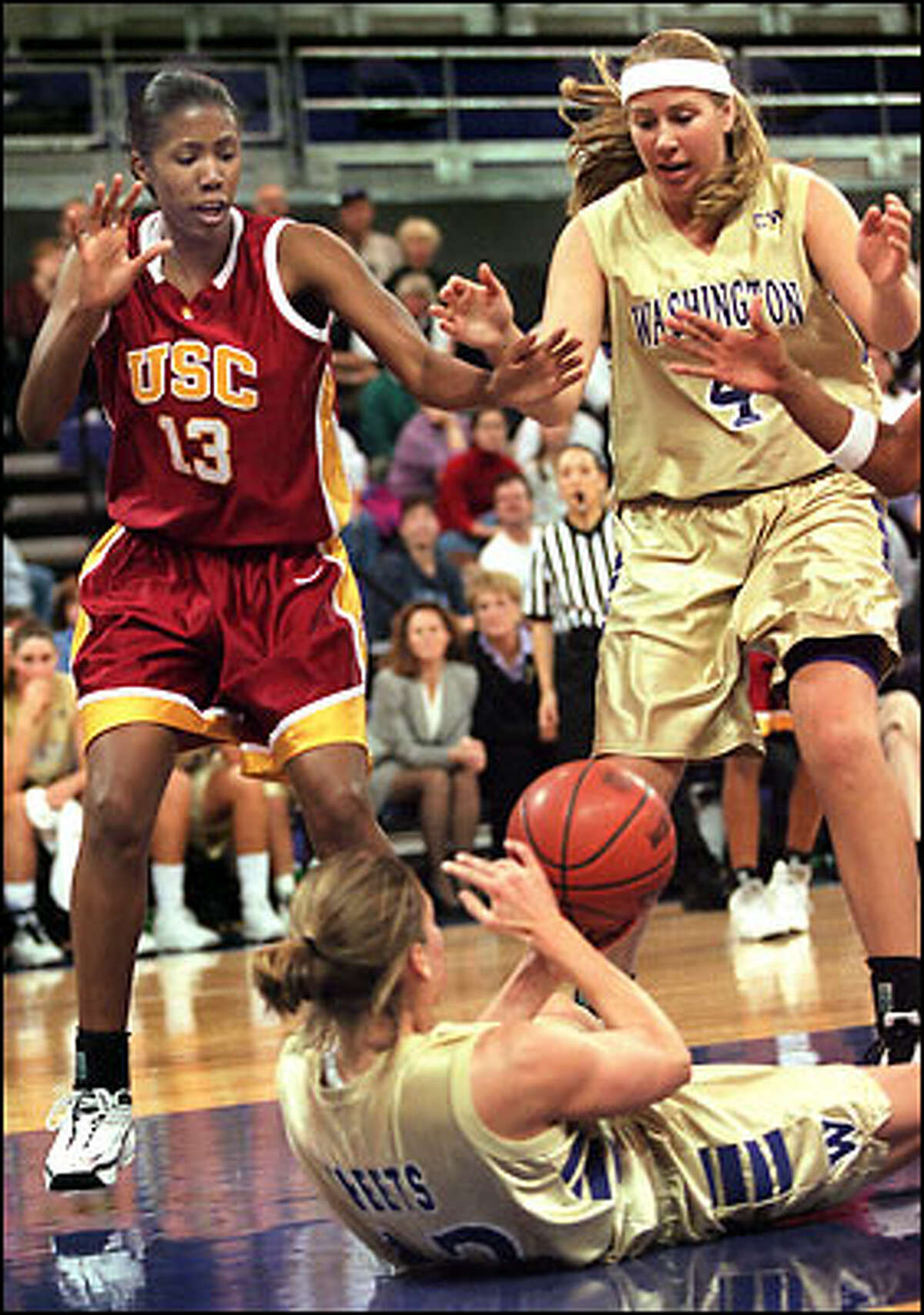 LeAnn Sheets looks for a place to pass the ball from a prone position as USC's Denise Woods and UW's Melissa Erickson await the outcome.