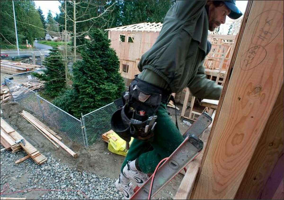 Doug McCallum climbs to a rooftop Friday to apply caulking on a house he's building in Kirkland, where city officials require the installation of chain-link fences, left, that protect a group of trees. A Western red cedar and cypress at the edge of the construction site also were saved. Protecting urban trees is a top priority for environmentalists in the upcoming session of the Legislature.