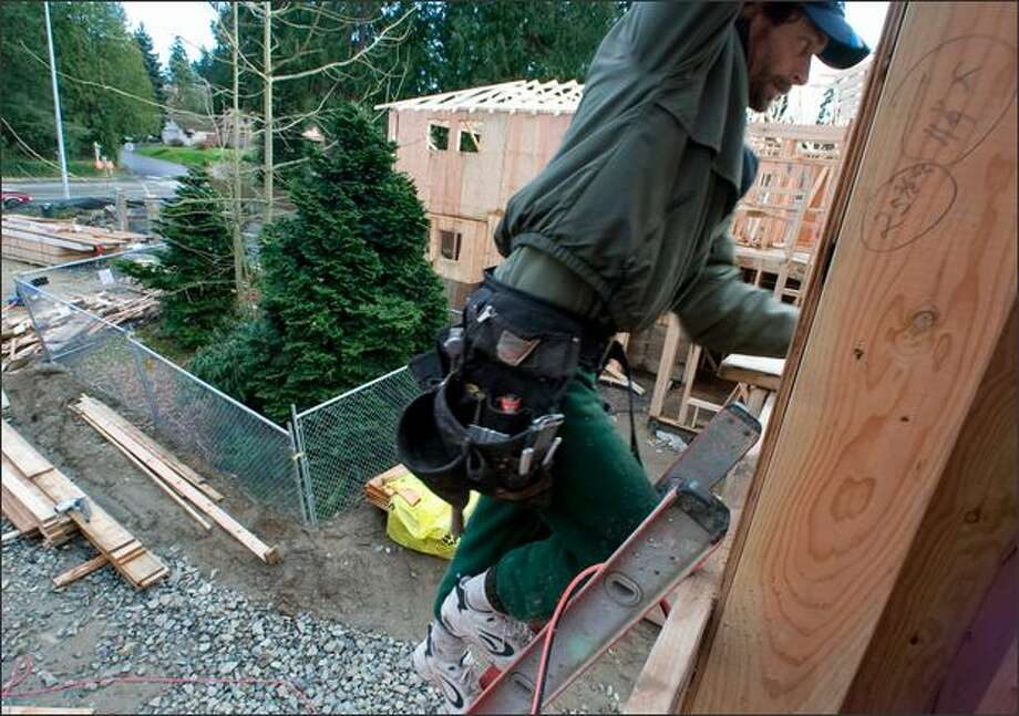 Doug McCallum climbs to a rooftop Friday to apply caulking on a house he's building in Kirkland, where city officials require the installation of chain-link fences, left, that protect a group of trees. A Western red cedar and cypress at the edge of the construction site also were saved. Protecting urban trees is a top priority for environmentalists in the upcoming session of the Legislature. Photo: Jim Bryant/Seattle Post-Intelligencer