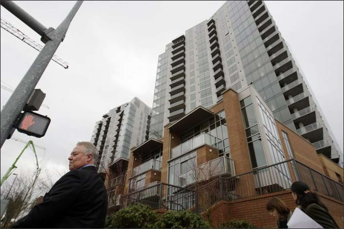 Dell Loy Hansen, chief executive of Wasatch Development Associates, leads a tour of the new Washington Square town houses and condominiums in Bellevue on Tuesday.