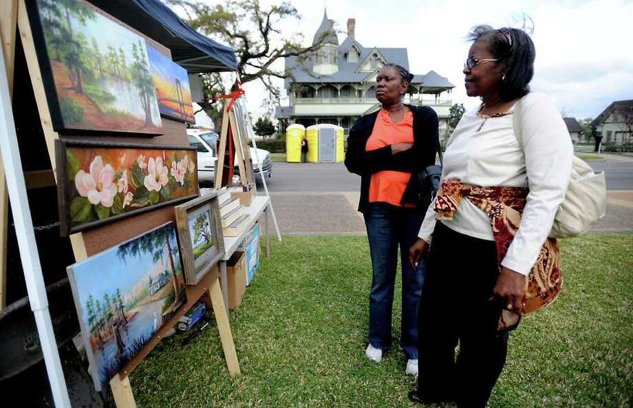 Pandora Kleckley and Laura Washington look over art on display at Barbara Haviland Fine Art's booth during the Art in the Park festival last year. Tammy McKinley/The Enterprise Photo: TAMMY MCKINLEY / Beaumont